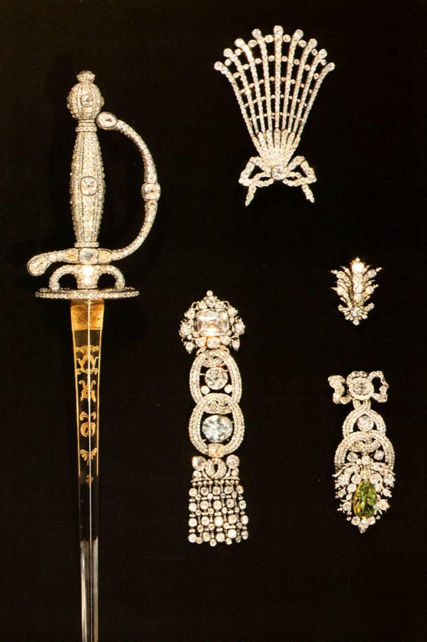Предметы из бриллиантового гарнитура - шпага, аграф для шляпы, аксельбант с саксонским Белым бриллиантом. Эгрет с Зеленым бриллиантом весом 41 карат. Украшение